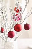 Rote Weihnachtskugeln hängen auf weissen Zweigen