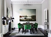 Glamorous dining room with green velvet upholstered chairs and a large landscape painting