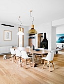 Large dining room with long table, designer chairs and XL pendant lights