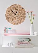 DIY-Wanduhr aus rustikalen runden Birkenhölzern über weißer Ablage mit Bücherstapel und Blumenvase