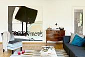 Wohnzimmer mit abstraktem Gemälde, alter Kommode und Samtsessel
