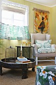 Small ethnic tables and wing-back chair below tapestry on board wall