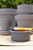 Grey painted flowerpots with a brush on a terracotta bowl in the foreground