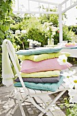 A stack of cushions on a chair on a sunny terrace
