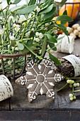 Metallkorb mit Mistelzweigen und einem Schneeflocken-Plätzchen (weihnachtlich)