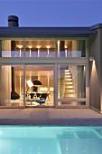 Pool vor zeitgenössischem Wohnhaus mit Innenbeleuchtung