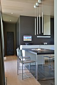 Minimalist dining table and chairs under pendant lamps and dark back wall in open-plan open kitchen