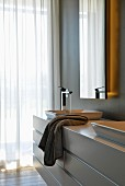 Custom washstand below mirror with integrated lights in elegant designer bathroom