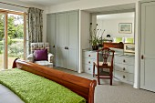 Wooden sleigh bed and pale grey fitted wardrobes with integrated dressing table in bedroom