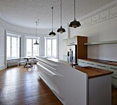 Minimalist, modern kitchen and artistically moulded half-height partition wall in period building with stucco frieze