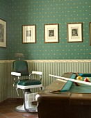 Old barber's chair and pool table in front of wall papered in classic style with different patterns on wall and dado