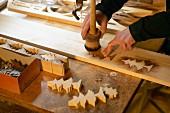 Umriss von Baumschablonen werden mit Beize aufs Holz übertragen