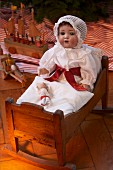 Old-fashioned Christmas toys: antique doll wearing nightcap in doll's bed