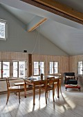 Biedermeier furniture in renovated dining room of old wooden house with exposed roof structure