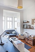 View across desk to sofa in window bay, wooden crate and wooden trunk