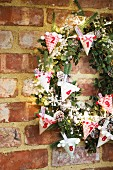 DIY Advent calender with numbered, decorated paper cones on green wreath on brick wall