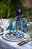 Sommerlich gedeckter Tisch mit blau-weißem Geschirr und Zweigen