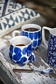 Two blue-patterned coffee cups on weathered wooden board