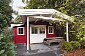 Red and white, DIY summerhouse with picnic bench and table on roofed terrace