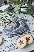 Ice-skate ornaments, mistletoe and biscuits on sheet music