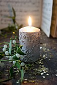 Lit candle with silver snowflake structure next to sprig of mistletoe