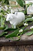 Sheep Christmas-tree bauble amongst sprigs of mistletoe on wooden surface