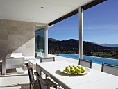 Dining table and chairs on sunny terrace with pool