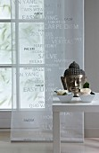 Head of Buddha and flowers in china bowls decorating table in front of window with transparent curtain panel