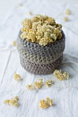 Dried everlasting flowers in crocheted basket on linen cloth