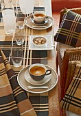 Tartan tablecloth on coffee table and matching scatter cushions on chairs