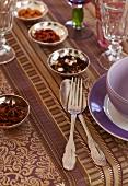 Elegant gedeckter Tisch mit violett-goldfarbener Tischdecke, Silberbesteck und Silberschälchen