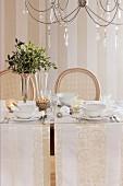 Festlich weihnachtlich gedeckter Tisch mit weissen Tischläufern und weißem Geschirr