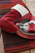 Festive arrangement on table in shades of red with tablecloth and felt Christmas stocking
