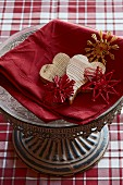 Wooden hearts and straw stars on red linen cloth on decorative dish