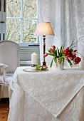 White damask tablecloth, table lamp and vase of tulips on table