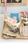Old sewing utensils in bowl with floral motif on stack of papers