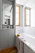 Kleines Bad mit Marmorwanne und schmalem Waschbecken