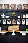 Black sideboard with various cake platters, storage jars and basket lanterns