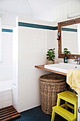 Laundry basket under vanity top next to yellow step stool in white bathroom with Scandinavian flair