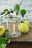Candle in mason jar with clip on rim and quinces on table