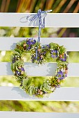 Heart-shaped wreath of flowers hung on bench backrest