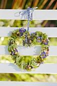 Herzförmiger Blütenkranz an Bank hängend