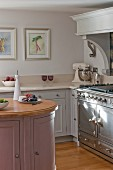 Panelled cabinets, pastel colour scheme, island counter and vintage-style cooker in rustic kitchen