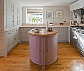 Pastel panelled cabinet doors, island counter and vintage-style cooker in rustic kitchen