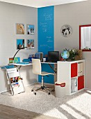 Work area with folding tables, shelves and blue chalkboard-paint stripe on wall