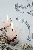 Candle lanterns made from ice with berries frozen in next to moose pastry cutter