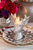 Eine brennende Kerze in Hirschform auf gold-gemusterten Tellern