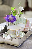 Gold-rimmed cups and delicate flowers on vintage-style silver tray