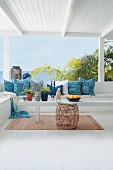Scatter cushions with variously patterned blue covers on bench on summery veranda