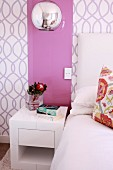 Modern, cubic bedside table below pink glass panel on patterned wallpaper